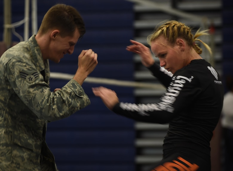 U.S. Air Force Senior Airman Ryan Hooper, 633rd Security Forces Squadron base defense operations center controller, trains with Valentina Shevchenko, UFC Bantamweight fighter, at Joint Base Langley-Eustis, Va., Dec. 8, 2016. Shevchenko not only trained with Airmen, but also visited JBLE units throughout the week as part of a military appreciation visit. (U.S. Air Force photo by Staff Sgt. Natasha Stannard)