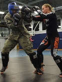U.S. Air Force Airman 1st Class Ramon Crespo, 633rd Security Forces Squadron entry control point monitor, spars with Valentina Shevchenko, UFC Bantamweight fighter, at Joint Base Langley-Eustis, Va., Dec. 8, 2016. Schevchenko visited the installation along with UFC fighters, Ben Rothwell and Lorenz Larkin as well as MMAradio hosts and Jacob 'Stitch' Durand. (U.S. Air Force photo by Staff Sgt. Natasha Stannard)
