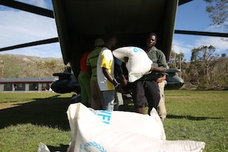 A Haitian man helps unload rice from the World Food Programme off of a CH-53 Super Stallion in Plaisance-du-Sud, Haiti, Oct 18, 2016. The Marines and sailors of with the 24th Marine Expeditionary Unit aboard USS Iwo Jima have been providing assistance to the U.S. government's civil humanitarian aid and disaster relief efforts in Haiti in wake of Hurricane Matthew. The 24th MEU is committed to remaining the nation's premier rapid crisis response force, providing the U.S. precious time in wake of a disaster, to coordinate a full-scale civil response. (U.S Marine Corps photo by Lance Cpl. Autmn S. Bobby)