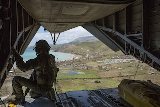 U.S. Marine Staff Sgt. Adam Stanley, a crew chief with Special Purpose Marine Air-Ground Task Force - Southern Command, deployed in support of Joint Task Force Matthew, looks out of the rear hatch of a CH-53E Super Stallion helicopter at the damage done by Hurricane Matthew at Les Anglais, Haiti, Oct. 13, 2016. After six days of supply drop operations, Joint Task Force Matthew has delivered over 349,000 pounds of supplies utilizing CH-53E Super Stallion and CH-47 Chinook helicopters. Joint Task Force Matthew, a U.S. Southern Command-directed team, is comprised of Marines, soldiers, sailors and airmen deployed to Port-au-Prince at the request of the government of Haiti to support the U.S. Agency for International Development's disaster relief operations in Haiti during the critical early stages after the island country was struck by Hurricane Matthew. (U.S. Marine Corps photo by Cpl. Kimberly Aguirre)