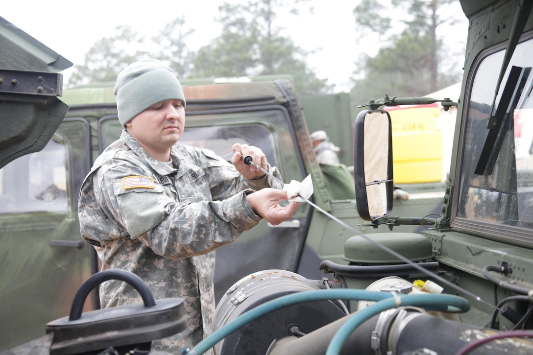 Spc. Corey Levi, 396th Medical Company, conducts preventive maintenance checks and services on a High Mobility Multipurpose Wheeled Vehicle, during an airborne operation, for the XIX Annual Randy Oler Memorial Operation Toy Drop, hosted by U.S. Army Civil Affairs & Psychological Operations Command (Airborne), at Luzon Drop Zone on Dec. 12, 2016. Operation Toy Drop is the world's largest joint and combined airborne operation and collective training exercise with paratroopers from eight partner-nations. (U.S. Army photo by Spc. Lisa Velazco/Released)