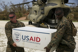 Lance Cpl. Alex Hurtado, heavy equipment operator, and Gunnery Sgt. Damian Herny, engineer chief with Special Purpose Marine Air-Ground Task Force – Southern Command, deployed in support of Joint Task Force Matthew, off load supplies for locals affected by Hurricane Matthew at Jeremie, Haiti, Oct. 9, 2016. In the third day of supply drop operations, JTF Matthew delivered bags of rice, cooking oil and other supplies utilizing CH-53E Super Stallion and CH-47 Chinook helicopters to provide humanitarian and disaster relief assistance in the aftermath of Hurricane Matthew. (U.S. Marine Corps photo by Sgt. Ian Ferro/Released)