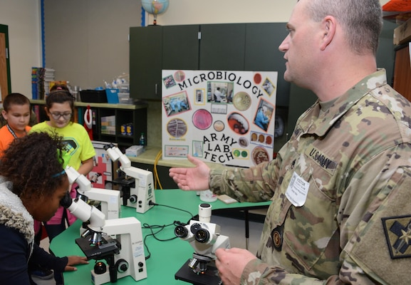 Staff Sgt. Christopher Magnuson from the 264th Medical Battalion at Joint Base San Antonio-Fort Sam Houston shows students how to see bacteria and pathogens under a microscope.