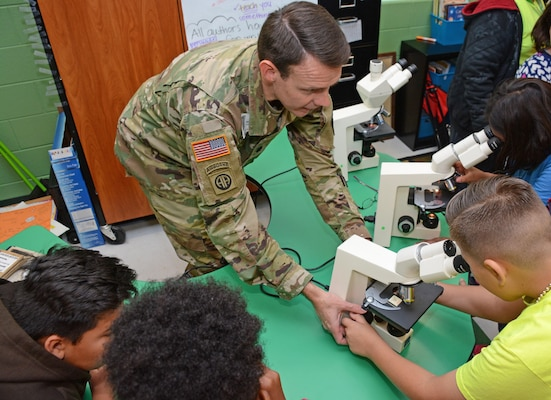 Lt. Col. Werner J. Barden, 264th Medical Battalion commander at Joint Base San Antonio-Fort Sam Houston, assists students viewing bacterial and pathogens under a medical microscope.