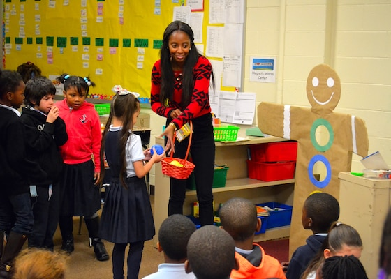 Darnesha King, an intern with the Construction and Equipment supply chain, leads Benjamin Franklin Elementary School students in a game during the annual Children's Holiday Party Dec. 8. Troop Support employees donated gifts for more than 200 students for the party.
