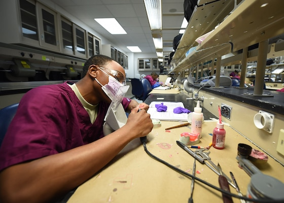 Airman Joshua Terry, a dental laboratory apprentice course trainee, practices fabricating dentures at the Medical Education and Training Campus on Joint Base San Antonio-Fort Sam Houston, Oct. 20, 2016. The 6-month technical training course is comprised of 5 different courses, each of which focuses on a specific skill set. While in training, the students are assigned to the 381st Training Squadron. (U.S. Air Force photo/Staff Sgt. Jerilyn Quintanilla)