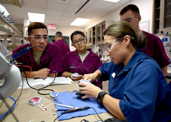Tech. Sgt. Elizabeth Blades, a dental laboratory apprentice course instructor, demonstrates a technique for carving out partial dentures at the Medical Education and Training Campus on Joint Base San Antonio-Fort Sam Houston, Oct. 20, 2016.  Blades is one of 10 Air Force instructors, all of whom are assigned to the 381st Training Squadron. (U.S. Air Force photo/Staff Sgt. Jerilyn Quintanilla)