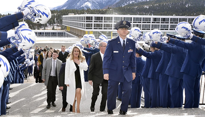 Brittany Bird (in white), wife of retired Capt. Carson Bird, walks up the steps to the Cadet Chapel while members of the Air Force Falcons hold their helmets aloft in salute to her husband, Dec. 9, 2016 at the U.S. Air Force Academy. Carson Bird, a 2008 Academy graduate and all-star cornerback, died Nov. 26, 2016, after battling Chondrosarcoma, a rare form of bone cancer. (U.S. Air Force photo/Jason Gutierrez)