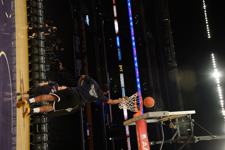 """Senior Airman Nyquetin Parks, Space and Missile Systems Center, reaches for the rafters to sink a 2- point jump shot. Military members of Los Angeles Air Force Base participated in the Lakers preseason """"Hoops for Troops"""" basketball clinics which was held at the Staple Center in Los Angeles on 11 Oct. 2016. The Airmen receive tips from Los Angeles Lakers player. (U.S. Air Force photo by Van De Ha)"""