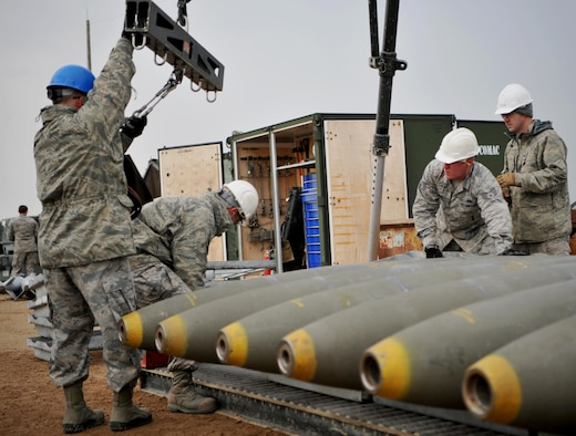 Enlisted Airmen and officers work together to load munitions at the munitions pad Dec. 13, 2016, at Beale Air Force Base, California. The munitions build is part of the Senior Officer Orientation course that immerses and familiarizes officers with the core training enlisted Airmen receive in the munitions career field. (U.S. Air Force photo/Staff Sgt. Jeffrey Schultze)