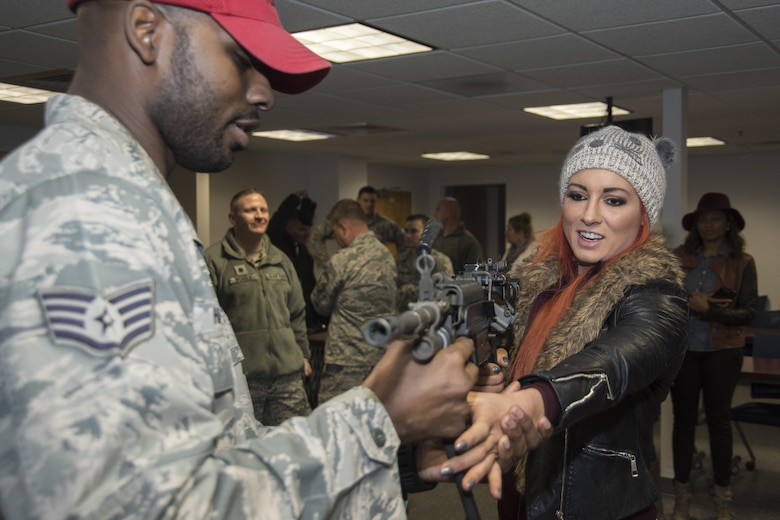 Staff Sgt. Eugene Harrison, 11th Security Forces Squadron member, provides basic weapons instruction to Becky Lynch, World Wrestling Entertainment Superstar, at Joint Base Andrews, Md., Dec. 13, 2016. In addition to laying out different weapons for the Superstars to view, security forces members provided demonstrations of the security forces military working dog section, combat gear and other aspects of the unit. (U.S. Air Force photo by Senior Airman Jordyn Fetter)