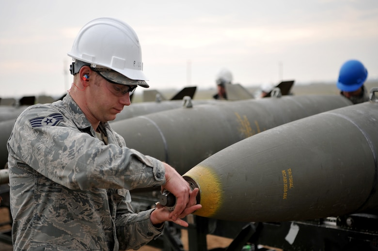Enlisted Airmen and officers work together to build munitions at the munitions pad Dec. 13, 2016, at Beale Air Force Base, California. The munitions build is part of the Senior Officer Orientation course that immerses and familiarizes officers with the core training enlisted Airmen receive in the munitions career field. (U.S. Air Force photo/Staff Sgt. Jeffrey Schultze)