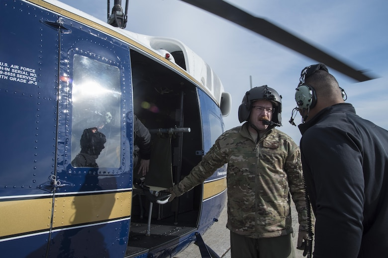 Tech. Sgt. Matt Dunn, 1st Helicopter Squadron flight engineer, directs Jason Jordan, World Wrestling Entertainment Superstar, into a UH-1N Iroquois at Joint Base Andrews, Md., Dec. 13, 2016. The squadron provided a rare tour of the National Capital Region aboard their aircraft for the Superstars, showing them national monuments like the Washington Monument, U.S. Capitol Building and Martin Luther King, Jr. Memorial. The Superstars visited JBA as a way to show their appreciation for the sacrifices military members have made, give back to the community and understand some of the missions that make up the armed forces. (U.S. Air Force photo by Senior Airman Jordyn Fetter)