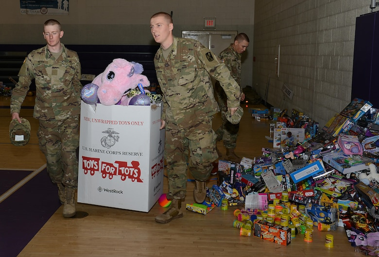 U.S. Army Soldiers assigned to 1st Battalion, 222nd Aviation Regiment, pack and carry donated toys to trucks for the U.S. Marine Corp's Toys for Tots program at Joint Base Langley-Eustis, Va., Dec. 8, 2016. Each year, the toy donation is followed by the annual holiday run. (U.S. Air Force photo by Staff Sgt. Teresa J. Cleveland)