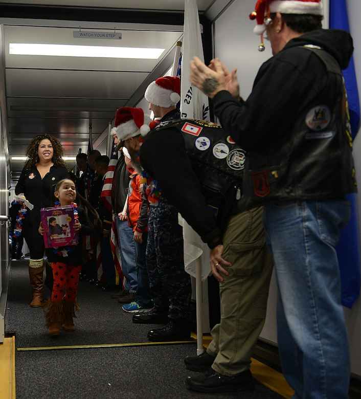 U.S. service members and the Virginia Patriot Guard cheer and escort Gold Star families onto their Snowball Express flight in Norfolk, Va., Dec. 11, 2016. This was the first year that Adriana Quintana, age 5, participated in the Snowball Express. (U.S. Air Force photo by Staff Sgt. Teresa J. Cleveland)