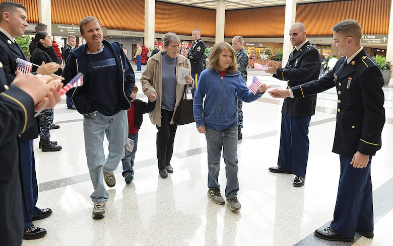 U.S. service members hand U.S. flags to Gold Star families as they leave for the Snowball Express at Norfolk International Airport, Norfolk, Va., Dec. 11, 2016. Gold Star families traveled to Dallas on a four-day, all expenses paid trip to thank them for their family member's sacrifice. (U.S. Air Force photo by Staff Sgt. Teresa J. Cleveland)