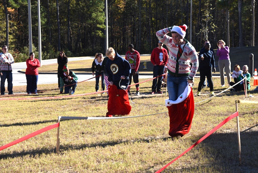 """Naval Health Clinic Charleston Executive Officer Capt. Kathleen Hinz, left, and Seaman Edward Duncan, a general duty corpsman, compete in """"Santa's Sack Race"""" during NHCC's """"Reindeer Games"""" competition Dec. 9 at NHCC. The team building activity included four six-person teams competing in five """"Minute to Win it""""- type challenges."""