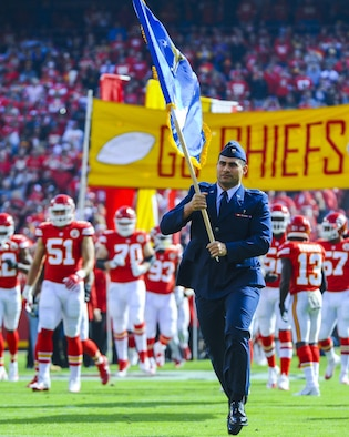 Capt. Fabian Tafuna, 22nd Air Refueling Wing chaplain, carries the Air Force flag before at a Kansas City Chiefs football game in honor of Veteran's Day, Nov. 6, 2016, Arrowhead Stadium, Mo. Before joining the Air Force, Tafuna played football as a fullback at Weber State University, Utah. (U.S. Air Force photo/Senior Airman Christopher Thornbury)