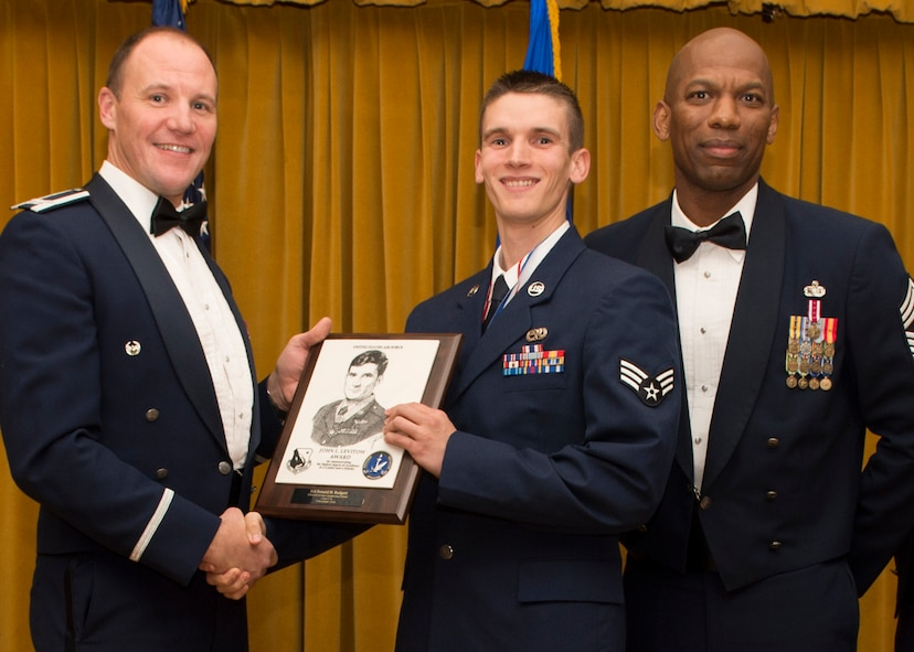 From left: Col. Jason Schott, 412th Test Wing vice commander, presents the Airman Leadership School John L. Levitow Award to Senior Airman Donald Badgett, 31st Test and Evaluation Squadron, along with Chief Master Sgt. Todd Simmons, 412th TW command chief. A graduation ceremony was held at Club Muroc Dec. 8 for ALS Class 17A. The Levitow award is presented to the student that demonstrated the most outstanding leadership and scholastic qualities. Selection is based on academic performance and assignment of points by peers and instructors. (U.S. Air Force photo by Joseph Gocong)