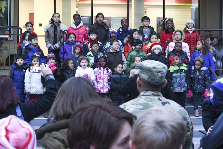 """Children from the Osan Chapel Children's Choir perform Christmas carols for the Christmas tree lighting ceremony at Osan Air Base, Republic of Korea, Dec. 8, 2016. Hundreds of service members and their families gathered in the """"Main Square"""" in front of the base theater to witness the lighting of the tree. (U.S. Air Force photo by Tech. Sgt. Rasheen Douglas)"""