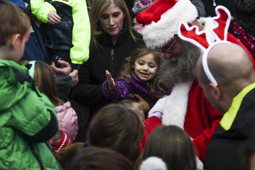 Santa Claus passes out candy to children during the Christmas tree lighting ceremony at Osan Air Base, Republic of Korea, Dec. 8, 2016. Osan children sang Christmas carols before Santa appeared, riding on a fire engine. (U.S. Air Force by Tech. Sgt. Rasheen Douglas)
