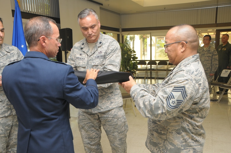 U.S. Air Force Col. Duke Ota, commander, 154th Mission Support group, and Lt. Col. Marc Gonsalves commander, 293rd Combat Communications Squadron case the unit flag together during the 293rd CBCS deactivation ceremony held at Joint Base Pearl Harbor-Hickam, Hawaii, Nov. 05, 2016. The deactivation ceremony is a time honored military tradition in which a unit is deactivated and cases the colors to signify the returning of the unit designation. (U.S. Air National Guard photo by Airman 1st Class Stan Pak/released)
