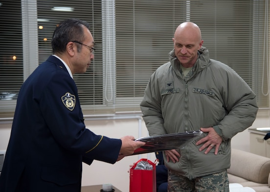 U.S. Air Force Col. R. Scott Jobe, right, the 35th Fighter Wing commander, presents his personal artwork as a gift to Katsuji Soma, left, Misawa City police station chief, during the End-Of-Year Traffic Safety and Crime Prevention Campaign in Misawa City, Japan, Dec. 14, 2016. This annual event showcases safety within the community of Misawa and combats crimes, alcohol related incidents, fraud and traffic accidents during the holiday season. (U.S. Air Force photo by Senior Airman Deana Heitzman)