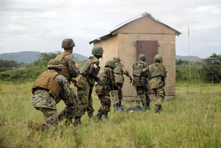 Marines with Special Purpose Marine Air-Ground Task Force Crisis Response-Africa watch as soldiers with an African partner nation rush a door after it was hit with an explosion at a training site, Nov. 23, 2016. Marines with SPMAGTF-CR-AF taught classes and participated in practical application exercises to enhance both nations' logistics and engineering capabilities during the nine-week training mission. (U.S. Marine Corps photo taken by Cpl. Alexander Mitchell/released)