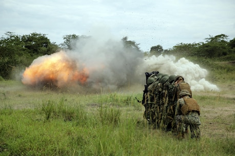 Marines with Special Purpose Marine Air-Ground Task Force Crisis Response-Africa stand in a stack behind a blast blanket, alongside soldiers with an African partner nation, as an explosion destroys a concrete wall during training, Nov. 23, 2016. Marines with SPMAGTF-CR-AF taught classes and participated in practical application exercises to enhance both nations' logistics and engineering capabilities during the nine-week training mission. (U.S. Marine Corps photo taken by Cpl. Alexander Mitchell/released)