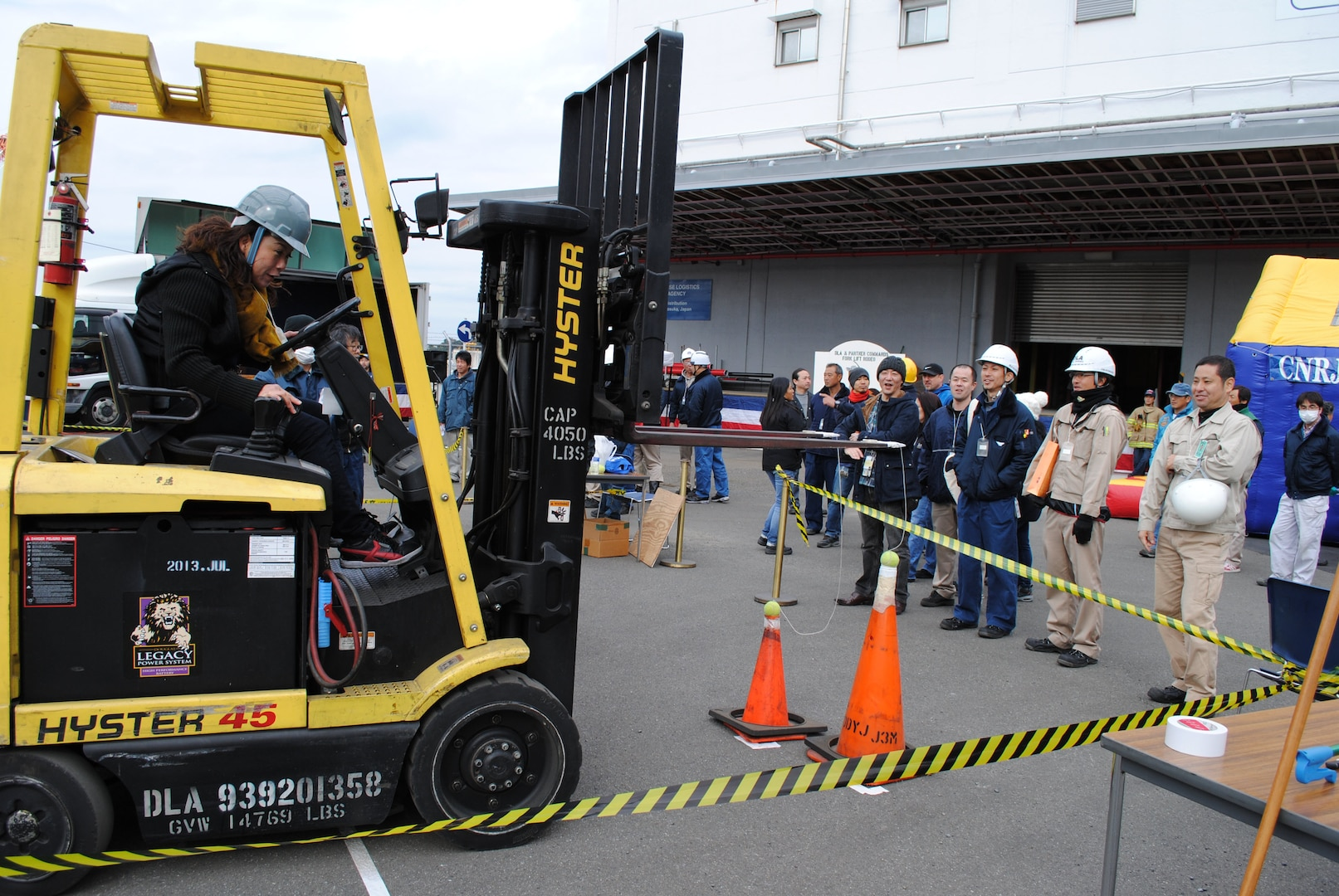 An employee works to land a tennis ball on a traffic cone, demonstrating precise equipment handling, during one of the events at the DLA Distribution Yokosuka, Japan, Forklift Rodeo.