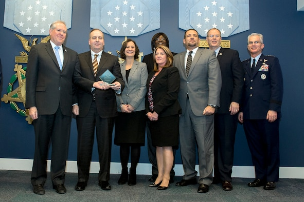 Frank Kendall, Under Secretary of Defense for Acquisition, left, presents members of the Resource Management Division with the Defense Acquisition Resource Management Award during a ceremony at the Pentagon on Dec. 8, 2016. Standing with them are Vice Chairman of the Joint Chiefs of Staff Gen. Paul J. Selva right, and Deputy Secretary of Defense Bob Work. (DoD photo)