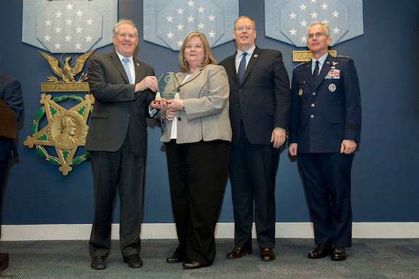 Frank Kendall, Under Secretary of Defense for Acquisition, left, presents Polly McCall with a Defense Acquisition Workforce Individual Award for contracting and procurement during a ceremony at the Pentagon on Dec. 8, 2016. Standing with them are Vice Chairman of the Joint Chiefs of Staff Gen. Paul J. Selva right, and Deputy Secretary of Defense Bob Work. (DoD photo)