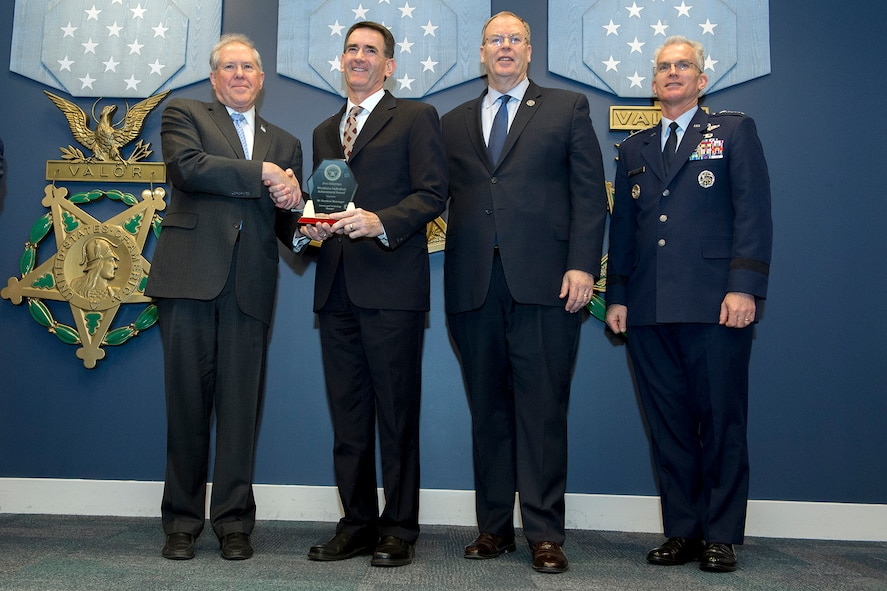 Frank Kendall, Under Secretary of Defense for Acquisition, left, presents Matthew Meininger with A Defense Acquisition Workforce Individual Award for science and technology management during a ceremony at the Pentagon on Dec. 8, 2016. Standing with them are Vice Chairman of the Joint Chiefs of Staff Gen. Paul J. Selva right, and Deputy Secretary of Defense Bob Work. (DoD photo)
