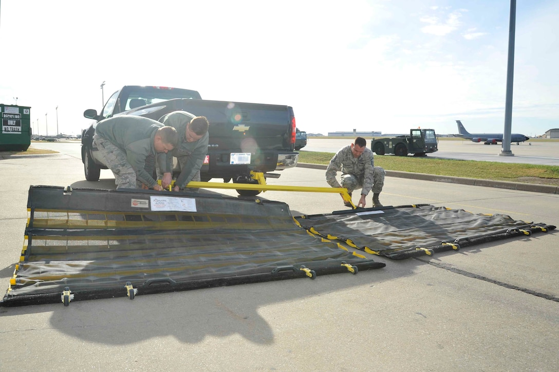 Senior Airman Patrick Bartosavage, 931st Aircraft Maintenance Squadron KC-46 equipment crew chief, Senior Airman Andrew Kruckman, 22nd AMXS assistant vehicle control officer, and Master Sgt. Erik Louviere, 22nd Maintenance Group FOD monitor, attach the base's new dual FOD system to a truck Dec. 2, 2016, at McConnell Air Force Base, Kan. The equipment, which is valued at approximately $11,000, was recently purchased to support the base's FOD prevention program and is used weekly to clear debris from the flightline. (U.S. Air Force photo/Airman 1st Class Erin McClellan)
