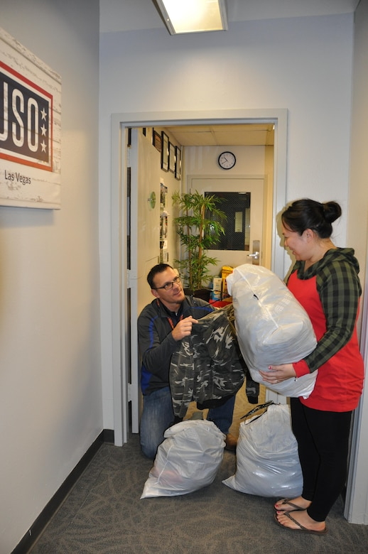 (Left) Clay Barber, Las Vegas USO RP/6 Scout, provides children's clothing to a member in need. The clothes were donated by another Nellis family. The USO provides a range of support to past and present Nellis members, and is also able to connect them with partner programs under the USO Transition 360 Alliance. (U.S. Air Force photo/Maj. Jessica D'Ambrosio)