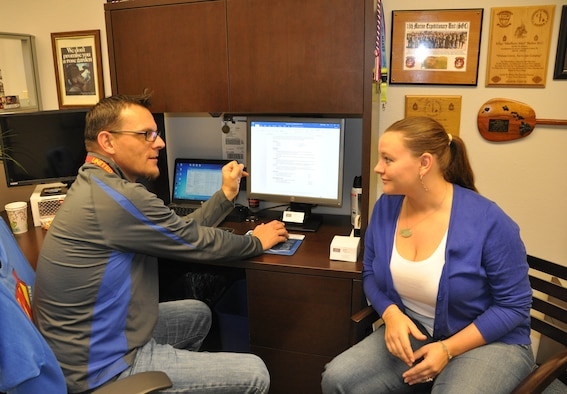 (Left) Clay Barber, Las Vegas USO RP/6 Scout, assists a transitioning base member with updating her resume. The USO is available inside the Community Commons building to provide support to the active duty, reservists, family members and veterans during life changes. (U.S. Air Force photo/Maj. Jessica D'Ambrosio)