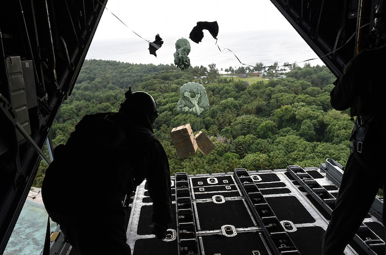 Staff Sgt. Andrew Thompson and Airman 1st Class Alejandra Vargas, loadmasters from the 36th Airlift Squadron, Yokota Air Base, Japan, push boxes of gifts off a C-130 Hercules over a remote Micronesian island during Operation Christmas Drop  Dec. 8, 2016. This year marks 65 years of Operation Christmas Drop, a humanitarian airlift operation, which provides joint airlift training opportunities for both peace and wartime efforts.