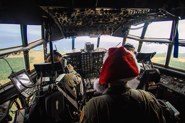 Crewmembers of a C-130 Hercules assigned to the 36th Airlift Squadron fly over remote a Micronesian island during Operation Christmas Drop 2016, Dec. 5, 2016. This year marks the 65th year of Operation Christmas Drop, which began in 1952, making it the world's longest-running airdrop mission.
