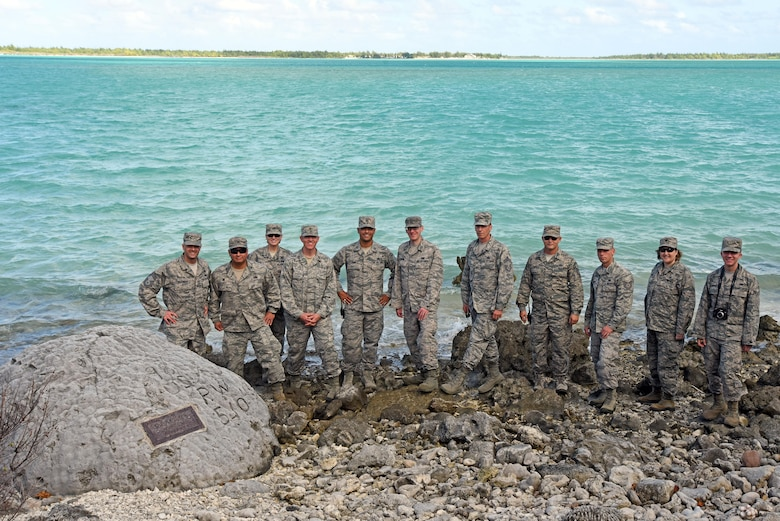 "WAKE ISLAND ATOLL--Guests who attended the Battle of Wake Island 75th anniversary ceremony including leadership from Pacific Air Forces Regional Support Center and 11th Air Force pay their respects and pose for a group photo at the ""98 Rock Memorial."" It is said that one of the 98 civilian prisoners of war etched a message into the rock; ""98 U.S. P.W. 5-10-43."" The 98 civilians were executed Oct. 7, 1943 by Japanese forces who controlled the island after the Battle for Wake Island in December 1941. (U.S. Air Force photo/Tech. Sgt. John Gordinier)"