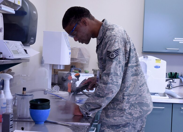Staff Sgt. Khodie Morgan, 341st Medical Operations Squadron dental laboratory technician, steam cleans a gold crown in the dental laboratory Dec. 5, 2016, at Malmstrom Air Force Base, Mont. The final process of creating a gold crown includes cleaning and polishing the compounds with the steamer. (U.S. Air Force photo/Senior Airman Jaeda Tookes)