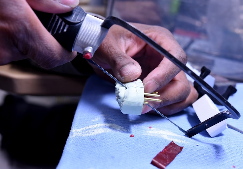 Staff Sgt. Khodie Morgan, 341st Medical Operations Squadron dental laboratory technician, sections a cast into dies for a gold crown using a hand saw in the dental laboratory Dec. 5, 2016, at Malmstrom Air Force Base, Mont. The die is the reproduction of the tooth consisting of a hard substance like metal, stone or resin. (U.S. Air Force photo/Senior Airman Jaeda Tookes)