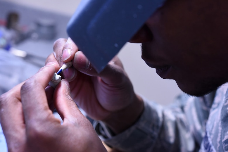 Staff Sgt. Khodie Morgan, 341st Medical Operations Squadron dental laboratory technician, refines a working die to make a crown in the dental laboratory Dec. 5, 2016, at Malmstrom Air Force Base Mont. When a cast is sectioned off into parts, each part is then referred to as a die. (U.S. Air Force photo/Senior Airman Jaeda Tookes)