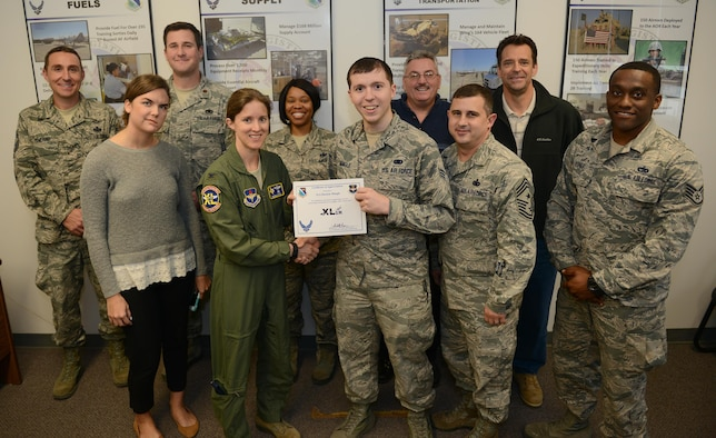 """Senior Airman Duston Mingle, 47th Logistics Readiness Flight Squadron logistics planner (front center), accepts the """"XLer of the Week"""" award from Col. Michelle Pryor (front left), 47th Flying Training Wing vice commander, and Chief Master Sgt. George Richey, 47th FTW command chief (front right), on Laughlin Air Force Base, Texas, Dec. 7, 2016. The XLer is a weekly award chosen by wing leadership and is presented to those who consistently make outstanding contributions to their unit and Laughlin. (U.S. Air Force photo/Airman 1st Class Benjamin N. Valmoja)"""