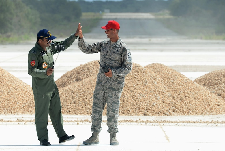 Indian Air Force Wing Commander Janardhana Reddy Neelam high-fives U.S. Air Force Master Sgt. Simon Zika, 554th RED HORSE Squadron, during a subject-matter expert exchange Oct. 25, 2016, at Northwest Field, Guam. The subject-matter expert exchange focused on airfield damage repair using folded fiberglass matting. These exchanges provide an opportunity for the U.S. Air Force and its international partners to enhance each other's capabilities, improve interoperability and fundamentally provide highly skilled coalition engineers for operations in a variety of environments. (U.S. Air Force photo by SSgt. Benjamin Gonsier/Released)