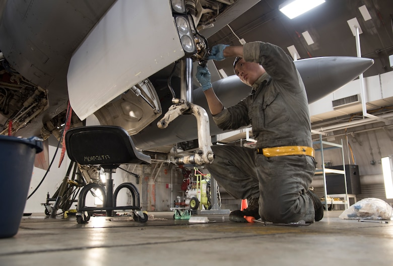 U.S. Air Force Senior Airman Harrison Lei, a 14th Aircraft Maintenance Unit crew chief, loosens a nose steering potentiometer at Misawa Air Base, Japan, Dec. 12, 2016. The potentiometer uses wires to control the steering of the aircraft. Loosening the nose steering allows maintainers to inspect the wires powering the aircraft landing gear ensuring wires are firmly connected. (U.S. Air Force photo by Airman 1st Class Sadie Colbert)