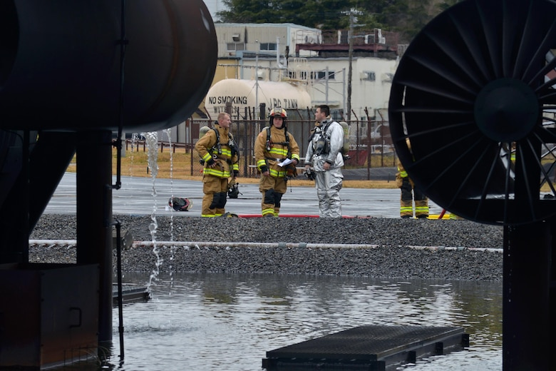 Firefighters with the 374th Civil Engineer Squadron discuss the previous training scenario at Yokota Air Base, Japan, Dec. 14, 2016. The training consisted of a training aircraft burning with two engine fires with leaking fuel spreading on the ground to simulate an aircraft on the runway needing assistance. (U.S. Air Force photo by Staff Sgt. David Owsianka)
