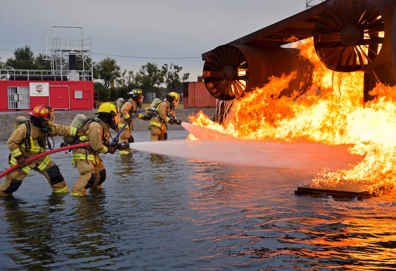 Firefighters with the 374th Civil Engineer Squadron put out a simulated aircraft fire during a training scenario at Yokota Air Base, Japan, Dec. 14, 2016. The training consisted of a training aircraft burning with two engine fires with leaking fuel spreading on the ground to simulate an aircraft on the runway needing assistance. (U.S. Air Force photo by Staff Sgt. David Owsianka)