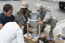 Members of the 18th Civil Engineer Squadron Water and Fuels Systems Maintenance team prepare a garbage disposal for installment at the Tee House Dec. 7, 2016, at Kadena Air Base, Japan. WFSM is responsible for installing equipment related to water and fuels to different areas of the base. (U.S. Air Force photo by Senior Airman Lynette M. Rolen/Released)