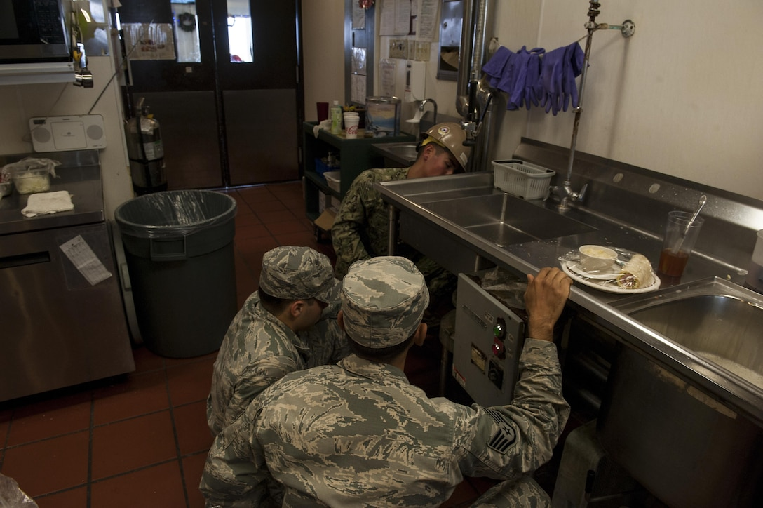 U.S. Air Force Staff Sgt. Jaime Gracias and Senior Airman Jacob Graham, 18th Civil Engineer Squadron Water and Fuels System Maintenance technicians, and U.S. Navy Seaman Richard Robledo, Naval Mobile Construction Battalion Five utilities construction man, take out an old garbage disposal unit at the Tee House Dec. 7, 2016, at Kadena Air Base, Japan. The WFSM technicians ensure different systems, such as garbage disposals, water systems for housing and plumbing are functioning properly or replaced entirely for safety. (U.S. Air Force photo by Senior Airman Lynette M. Rolen)