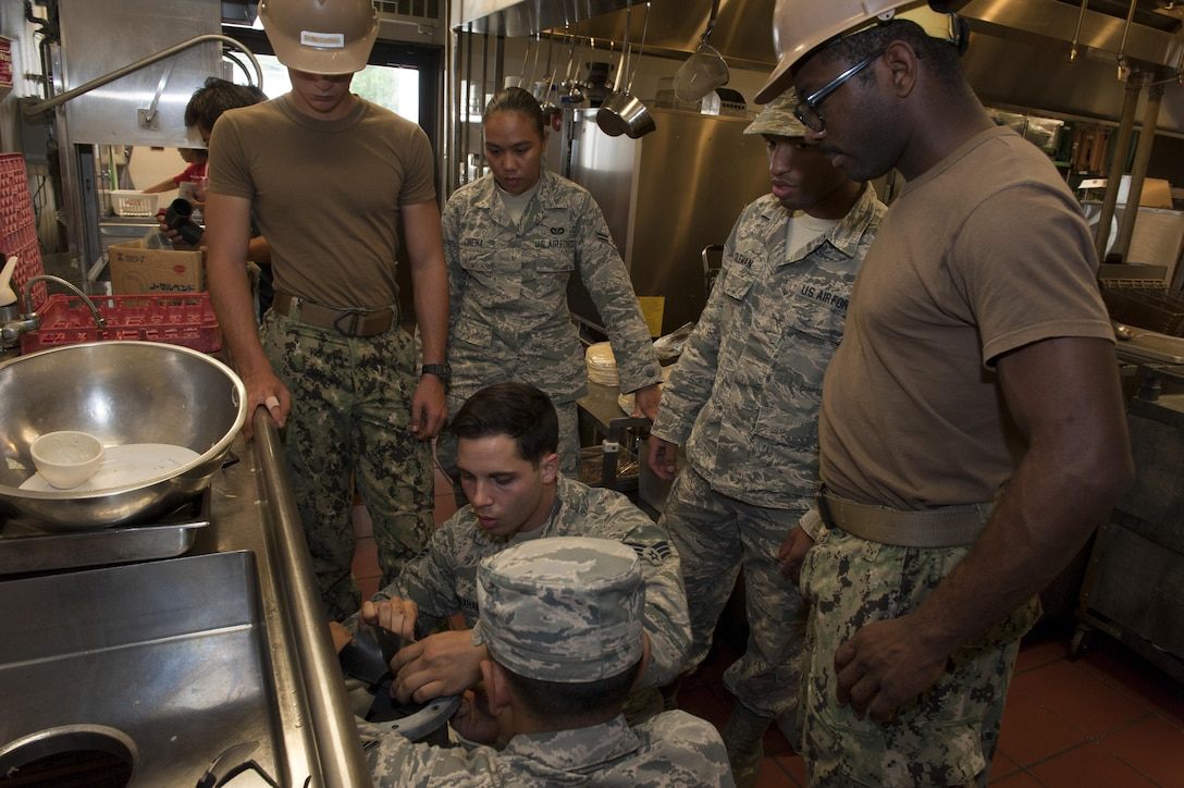Members of the 18th Civil Engineer Squadron Water and Fuels Systems Maintenance team install a new garbage disposal unit in the Tee House Dec. 7, 2016, at Kadena Air Base, Japan. The Tee House is a historical building on Kadena and first opened in January of 1967. (U.S. Air Force photo by Senior Airman Lynette M. Rolen/Released)